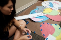 Resident Assistants, such as junior, Jessica Deng, spend some of the little time that they have during training week to hang up floor decorations.