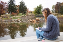Physics and math double major Mary Aronne studying differential equations by the revamped pond.